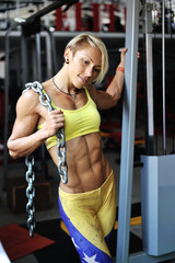 Muscular bodybuilder woman holding chains