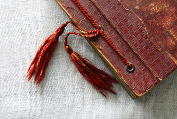 Old red photo album with tassels on canvas background