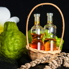 Aromatic spa concept of bottles essential oil in basket, flower,