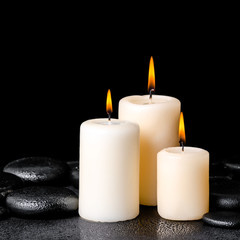 spa concept of white candles on zen basalt stones with drops, cl