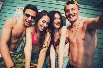 Multiracial fiends make fun selfie at beach house on vacation