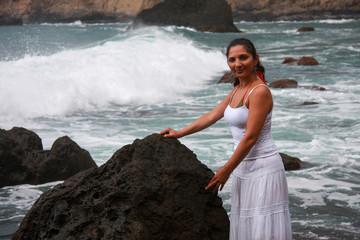 Frau in weißem Kleid an Fels