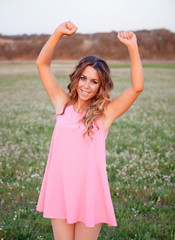 Girl with pink dress celebrating something in a field full of fl