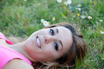 Blonde woman lying in a beautiful field full of flowers