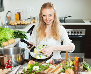 Smiling girl cooking fish  in frying pan at  kitchen