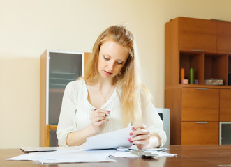 serious blonde woman staring financial documents