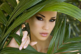 Makeup. Sexy beautiful woman hiding behind the palm leaves. Beau