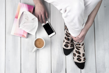 Woman sitting on floor with coffee, smartphone and tissues
