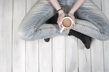 Teenage girl sitting on floor holding a coffee cup