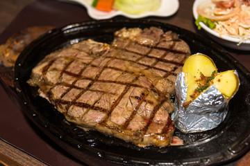 Premium American prime rib steak on a metal plate.