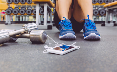 Sporty man sitting with dumbbells and smartphone in gym floor