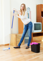 Positive long-haired housewife   with mop