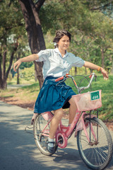 Thai Schoolgirl playing risky on a bicycle, in the park in vinta