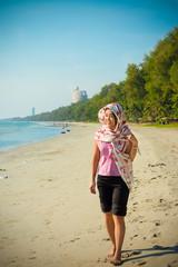 Asian Thai girl is walking along the beach coast of Rayong, Thai