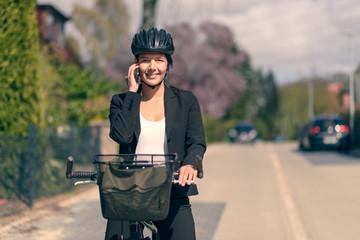 Geschäftsfrau telefoniert und steht mit ihrem Fahrrad