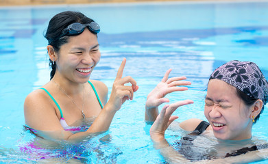 Two Asian girls are flicking water to one another in the swimmin