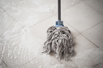 Floor cleaning with mob and cleanser foam.