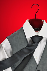 Mens white shirt, grey tie and waistcoat on red background.