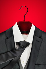 Mens dark grey suit closeup on clothes hanger on red background.