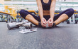 Sporty woman sitting with dumbbells and smartphone in gym floor