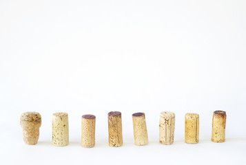 row of wine corks on white background