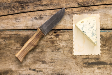 Piece of blue cheese with knife on wood background