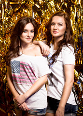 two sexy brunette girls posing against golden background