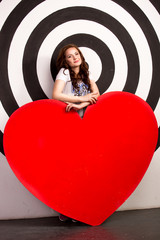 smiling woman holding big red heart in studio