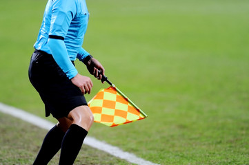 Assistant referee signaling with the flag