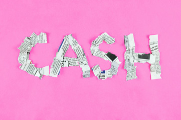 Word cash made of newspaper pieces on bright pink background.