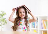 Fototapety preschooler  kid girl with book over her head
