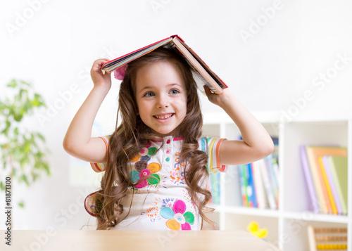 preschooler  kid girl with book over her head - 81871300