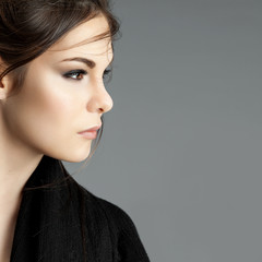 Portrait of a young cute girl in profile on a gray background
