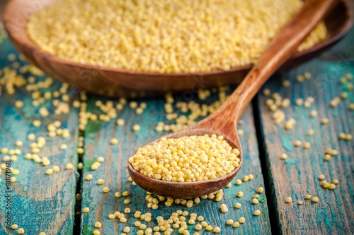 organic millet seeds in a wooden spoon closeup - 81871968