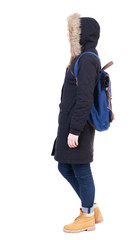 Back view woman in winter jacket with  backpack