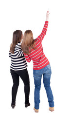 Two long haired friendly women pointing .