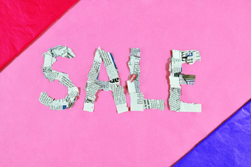 Word sale made of newspaper pieces on colourful background.