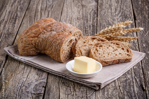 Tuinposter Brood Tasty bread with wheat on wooden background.