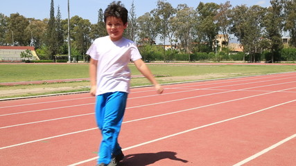 Little boy running outdoor and smiling to camera