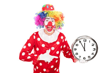 Young male clown holding a big wall clock