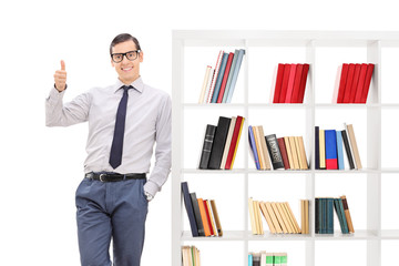 Young man giving thumb up and leaning on bookshelf