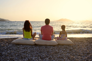 Happy family sitting on cushion posing on  beach sunset