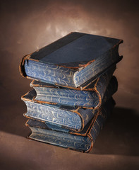 stack of old books on a painted canvas backdrop