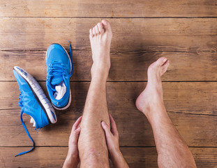 Injured runner sitting on a wooden floor background