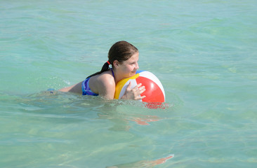 Smiling girl with  ball relaxing in beautiful  ocean.
