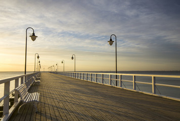 Drewniane molo nad Morzem o wschodzie słońca