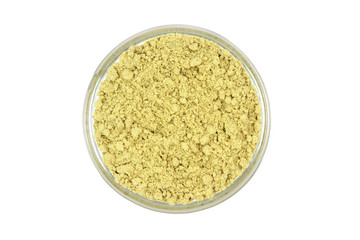 a handful of mustard powder in a glass cup on a white background
