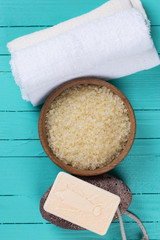 Sea salt in bowl  and towels on blue wooden background