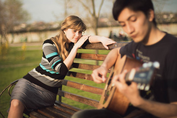 young guy playing guitar girl in the park