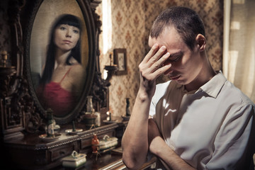 Man in grief on the vintage mirror background